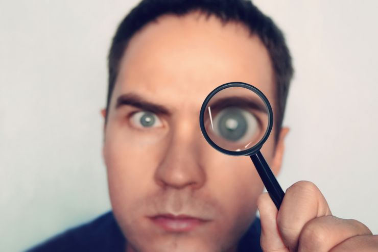 Man on white background curiously looks through the magnifying glass. Male fuzzy eye magnified through the loule. Person uses magnifier to look closely at some object. Detective search for evidence