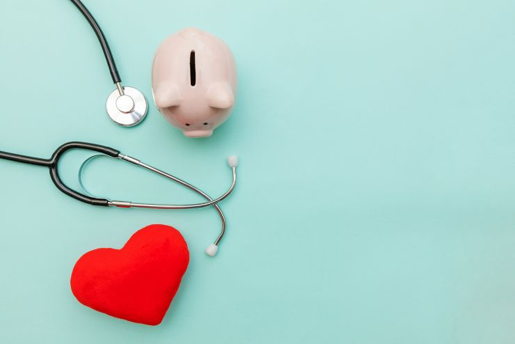 Medicine doctor equipment stethoscope or phonendoscope piggy bank and red heart isolated on trendy pastel blue background. Health care financial checkup or saving for medical insurance costs concept