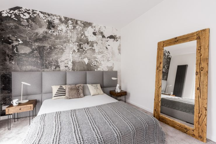 Grey king-size bed in a spacious bedroom with an abstract wallpaper on the wall and a large wood framed mirror