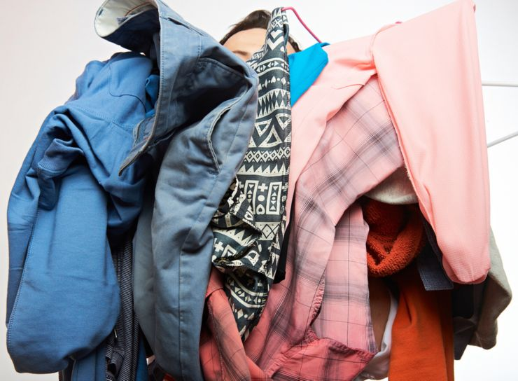 Man holding pile of clothes. Men behind dirty dress wear isolated on white background