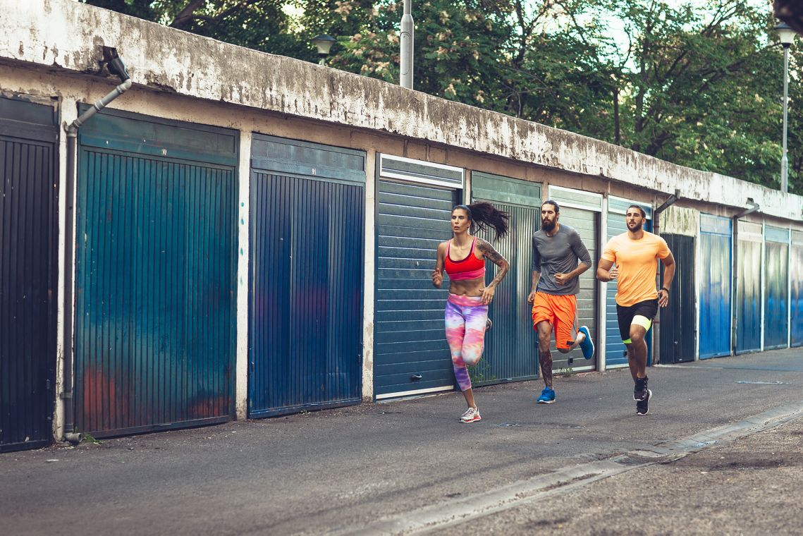 Sportswoman and two sportsmen jogging together.