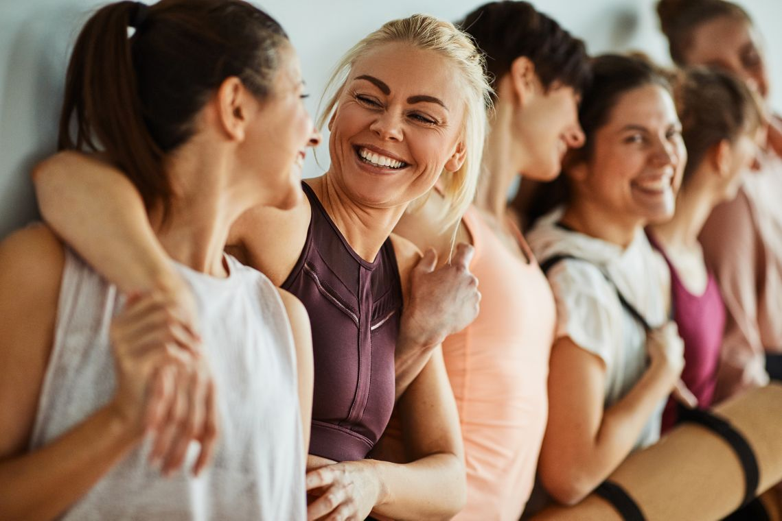 Smiling friends standing arm in arm together after a yoga class together in a health club
