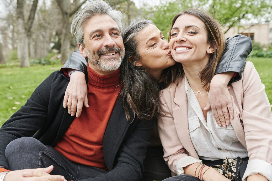 Mature woman playfully kissing her friends on the cheek while sitting together on some grass in a park