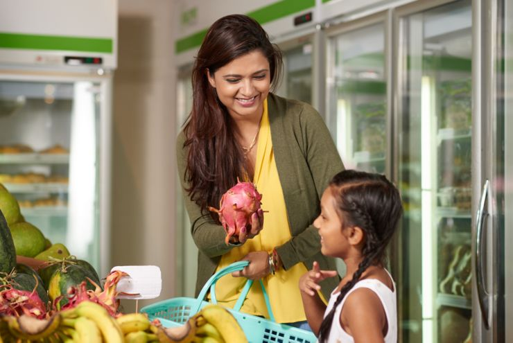 Smiling Indian woman showing dragon fruit to her daughter