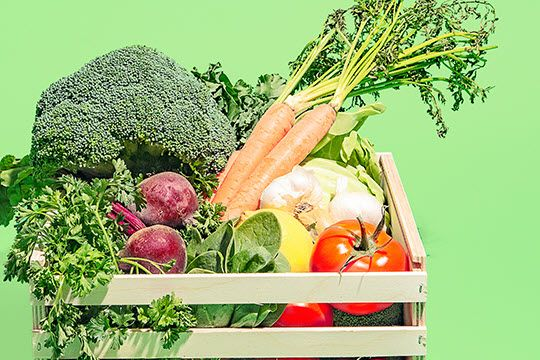 Juice Plus+ vegetable blend capsule alongside a box of veggies