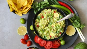 Delicious bowl of traditional   Mexican Guacamole, nachos and guacamole ingredients: Avocado, onion, cilantro, hot pepper tomatoes and lime.Top view, flat lay. Fresh, raw, vegetarian dish, copy space