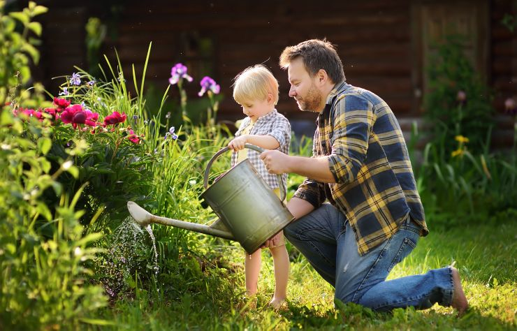 Middle age man and his little son watering flowers in the garden at summer sunny day. Gardening activity with little kid and family