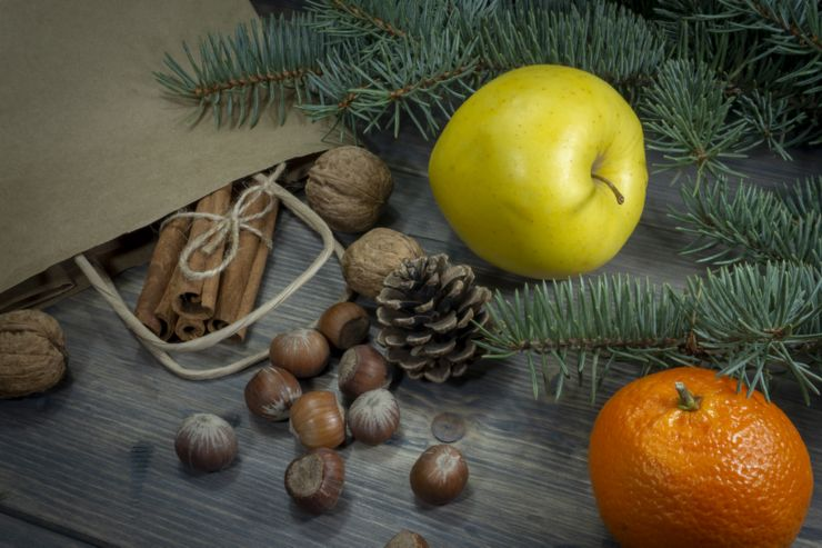 Various nuts, cinnamon yellow apple and clementine as concept of holiday groceries, spread on wooden table out of paper shopping bag, viewed in close-up from high angle with fir tree branch