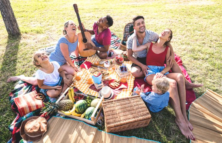 High angle top view of happy families having fun with kids at pic nic barbecue party - Multiracial love concept with mixed race people playing with children at public park - Warm retro vintage filter