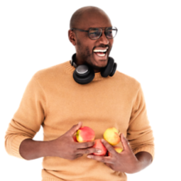 A man laughing while holding Apples