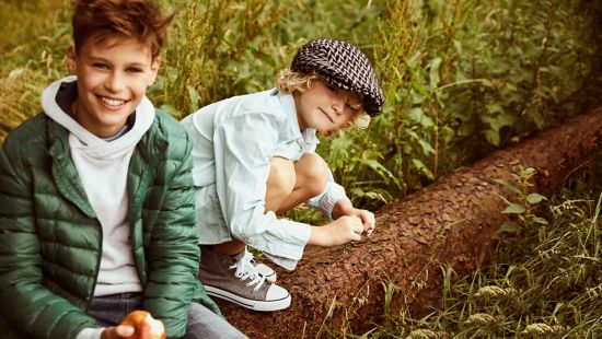 Two kids smiling and eating apples