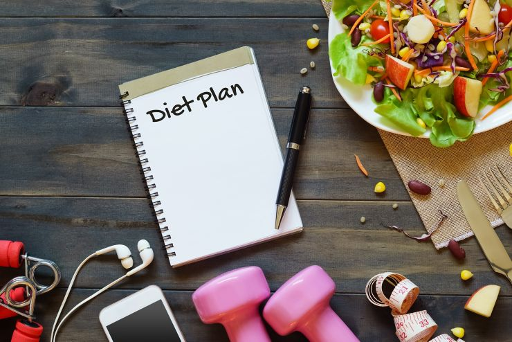 Top view on wooden table with Salad, dumbbells, measure tape, smartphone and  notebook with diet plan text. Diet, fitness and healthy eating with healthy recipes concept.  Copy space for text or your diet plan.