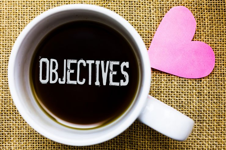 Text sign showing Objectives. Conceptual photo Goals planned to be achieved Desired targets Company missions Tea time coffee cup office typing work jute rough background love heart