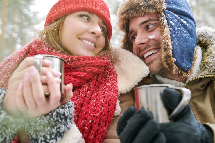 Head and shoulders portrait of loving young couple enjoying hot cocoa during date in beautiful winter forest and looking at each other tenderly